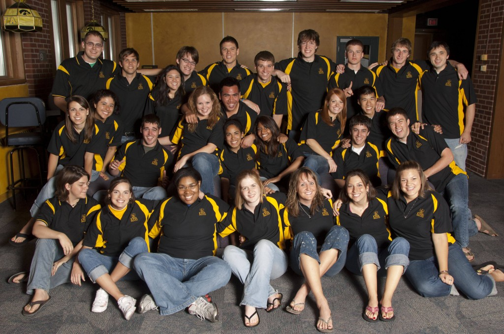 A large group of students, from the University of Iowa, wearing matching black and gold uniforms.