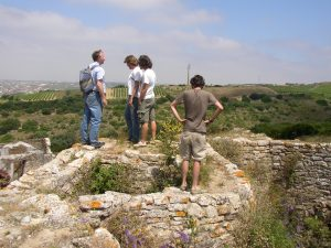 Michael Kunst (left), director of Zambujal excavations, showing Bolores crew members one of the towers at Zambujal