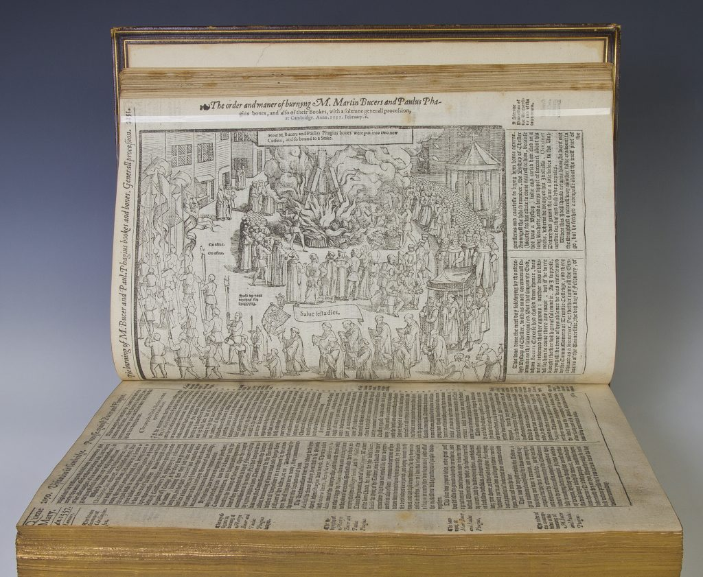 Book opened to display illustration of a crowd people gathered around a fire