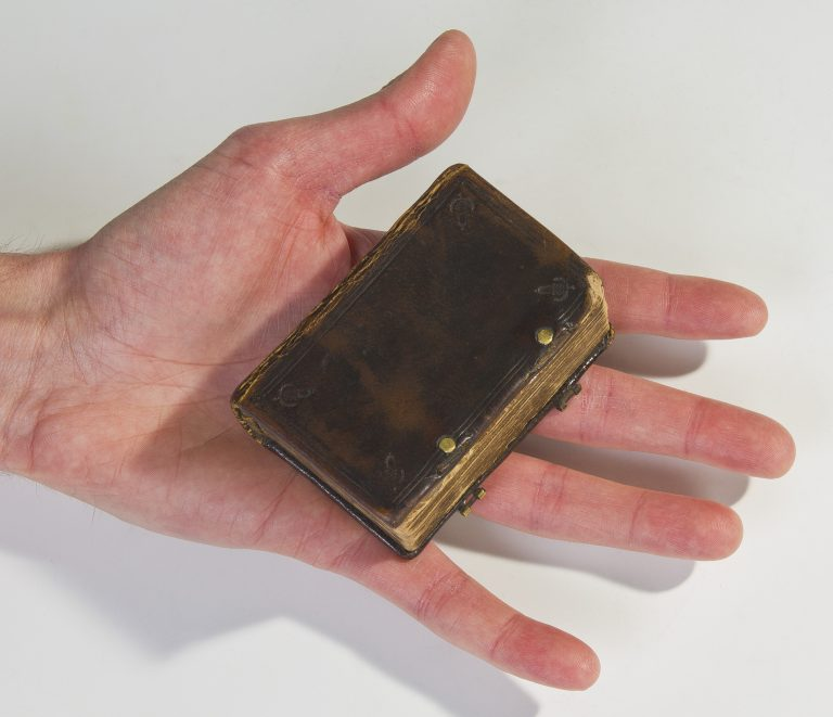 Palm-sized pocket bible held in hand